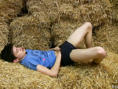 Young Czech boy lying on the hay and playing with his cock