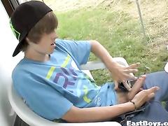 Cute teen guy is sitting outdoors and pleasuring hot masturbation