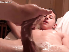 Freaky gay records teen twink lying on the bed and enjoying handjob