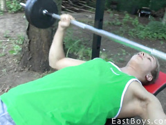 Sweet and sexy blonde twink is lifting weight outdoors