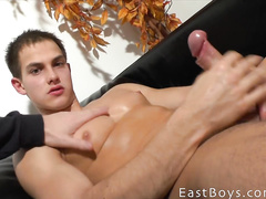 Adorably cute twink pleasantly masturbating cock on couch