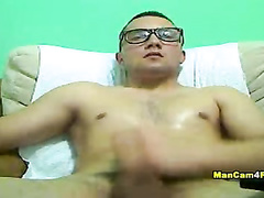 Twink in glasses is watching porn and jerking off his dick